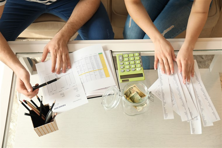 young couple working on their budget and finances with a calculator and a independent financial advisor