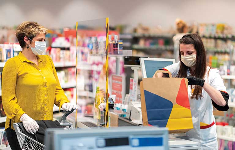 Supermarket cashier with mask is supported by her employer with financial wellbeing benefits.