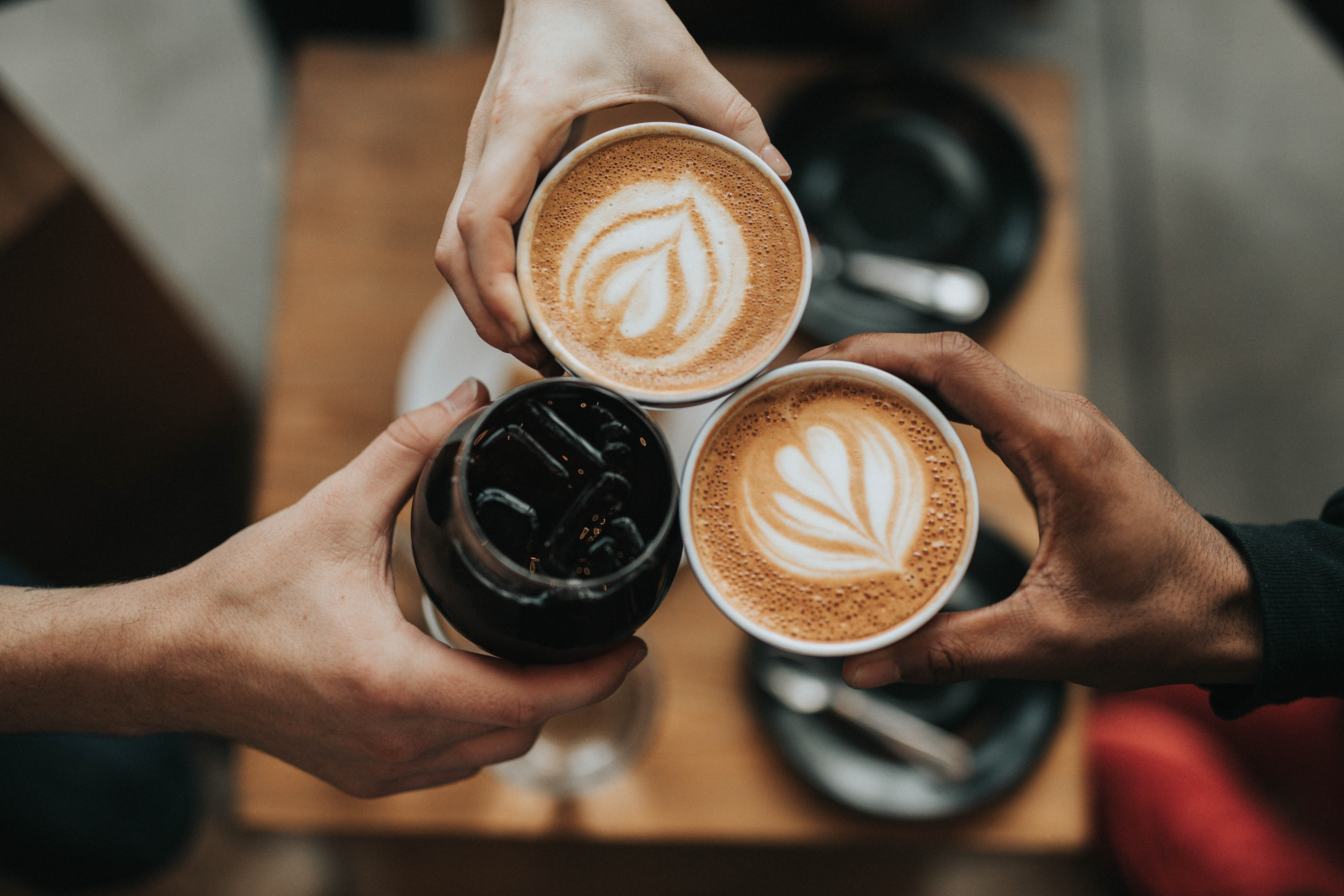 Three employees in a hybrid workplace cheers their morning coffee