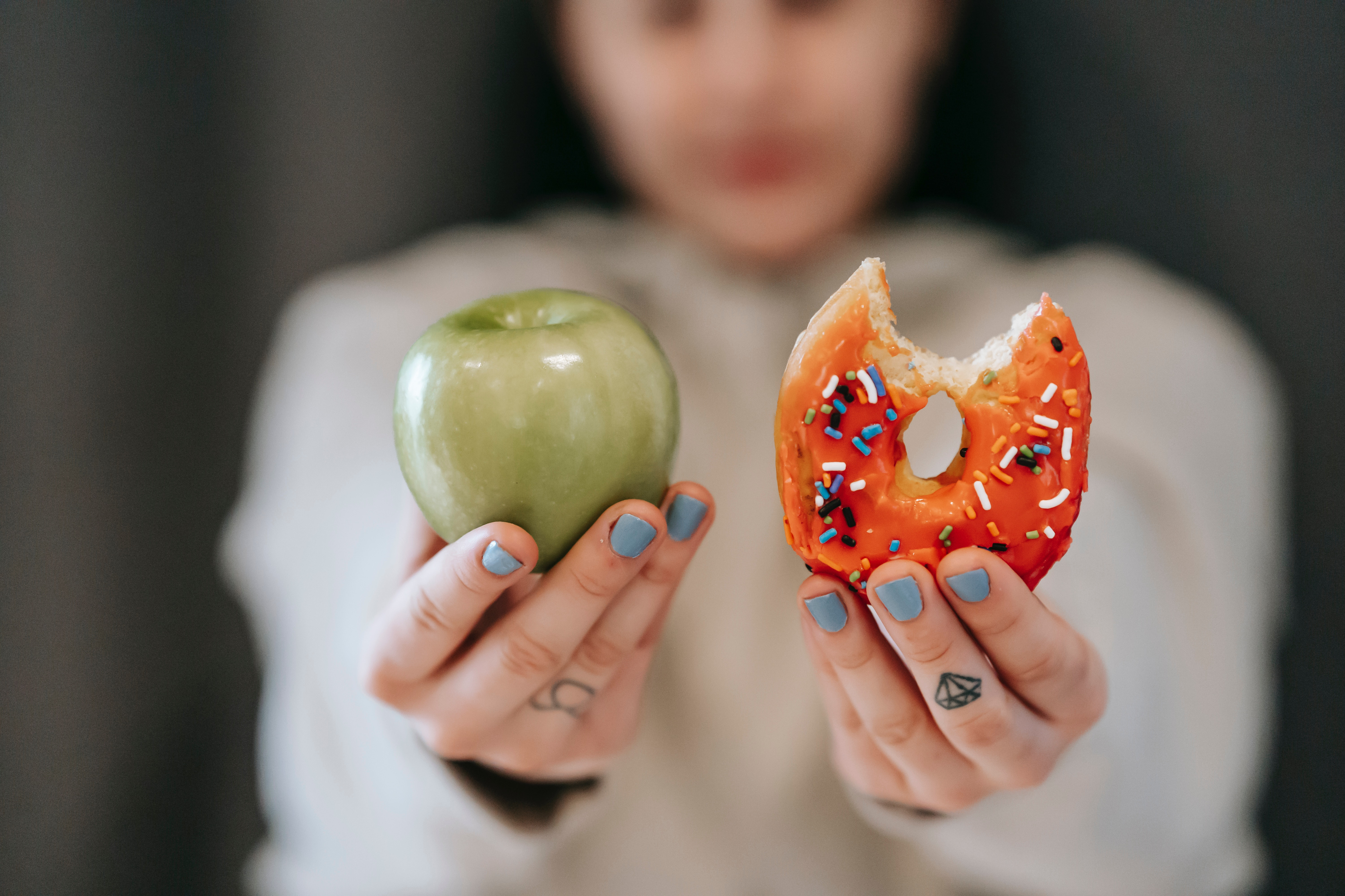 An employee who's physical wellbeing is tied to financial wellness holds a green apple and orange donut