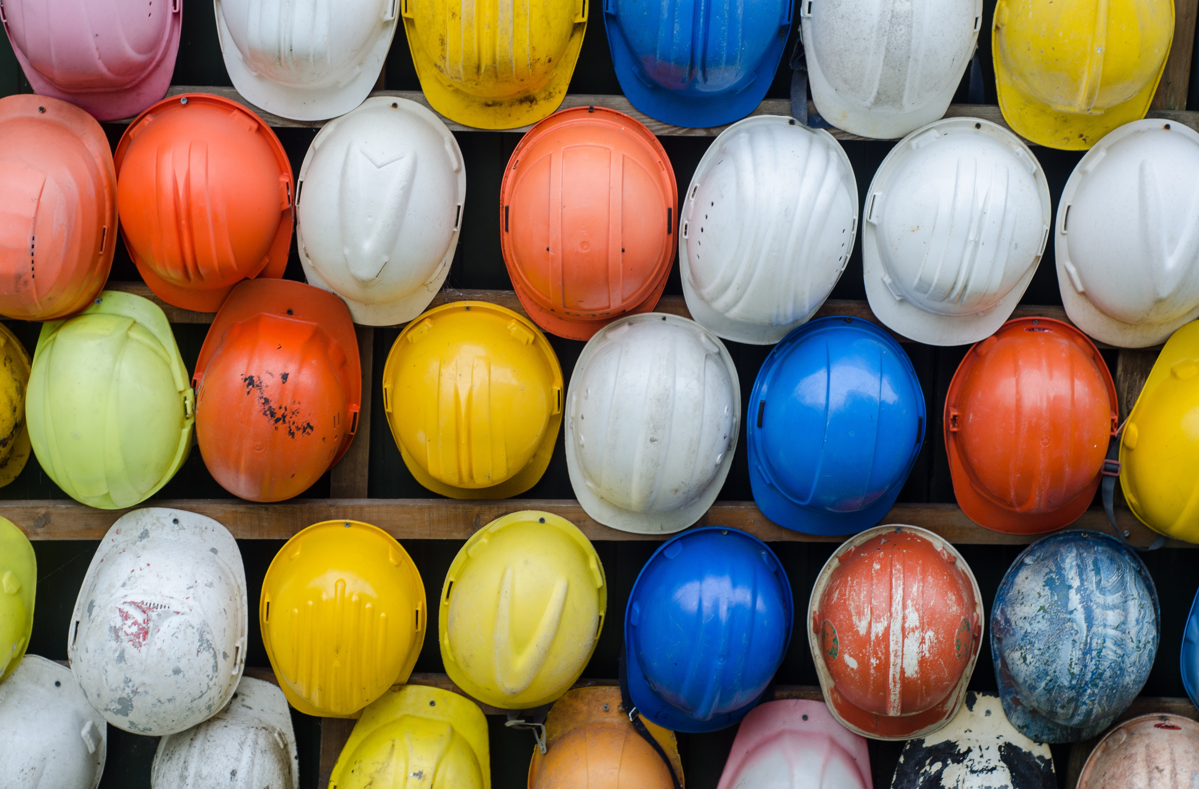 A photo of colorful hardhats for construction and manufacturing companies financial wellbeing program guide